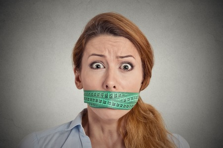 mouth closed: Portrait unhappy young woman with green measuring tape covering mouth isolated grey wall background. Dieting lifestyle concept