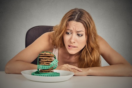 bulimia: Portrait young unhappy woman craving sugar sweet cookies but worried about weight gain sitting at table isolated grey wall background. Human face expression emotion. Diet nutrition dilemma concept