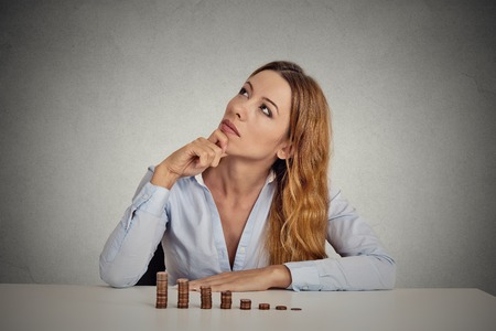 budget crisis: Portrait thoughtful young business woman corporate executive sitting at table with growing stack of coins isolated grey wall office background. Face expression. Financial economy doubt concept Stock Photo