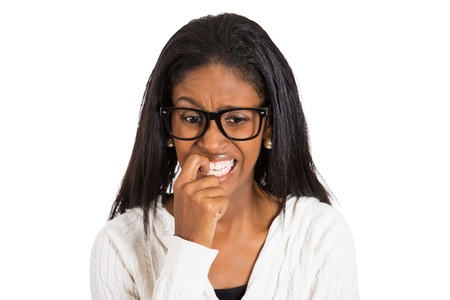 insecure: Closeup portrait headshot nervous woman with glasses biting her fingernails craving for something, anxious, isolated white background. Negative human emotion facial expression feeling body language Stock Photo