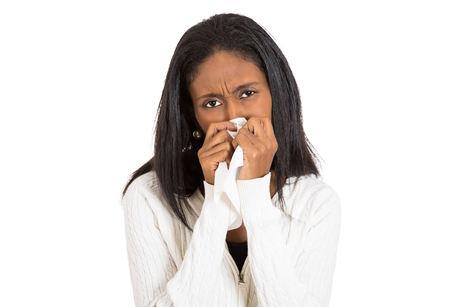 sneeze: Closeup portrait sick young woman student, worker, employee with allergy, germs, cold, blowing nose with kleenex, looking miserable, unwell very sick, isolated on white background. Flu season, vaccine Stock Photo