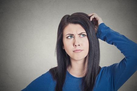 근접 촬영 초상화 얼굴 젊은 여자 절연 회색 벽 배경을 찾고 무엇인가에 대해 깊이 공상 생각, 머리를 긁적. 인간의 얼굴 표정의 감정 느낌 상징 서명 스톡 콘텐츠