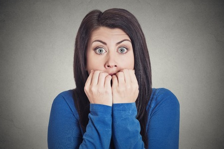 conflictos sociales: Headshot Retrato del primer joven mujer nerviosa indeciso inseguro morder sus uñas antojo de algo o ansiosos, aislados fondo gris de la pared. Emociones humanas negativas sentimiento expresión facial Foto de archivo