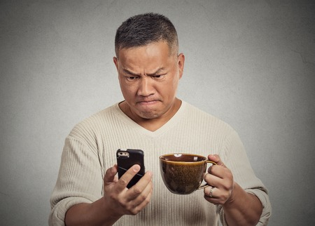Closeup portrait worried angry frustrated man reading bad news sms on smart mobile phone drinking holding cup coffee tea isolated grey wall background. Human face expression emotion reaction