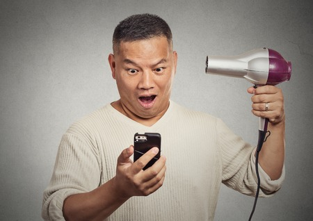 alopecia: Closeup portrait shocked surprised man looking on smartphone holding hairdryer something blows his mind isolated grey background. Face expression emotion. Stressful life breaking mind blowing news Stock Photo