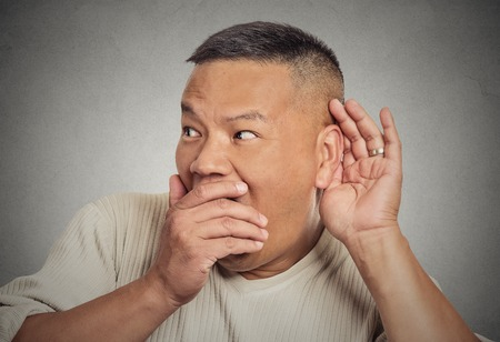 secretly: Headshot of man, hand to ear gesture trying secretly listen in on juicy gossip conversation news privacy violation, shocked by what he hears, isolated on grey background. Face expression, emotion Stock Photo