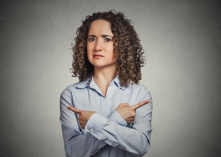 indecision: Indecision confusion. Portrait confused young woman pointing in two different directions not sure which way to go isolated grey background. Negative emotion facial expression feeling body language