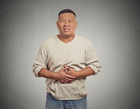 クローズ アップ肖像画悲惨な動揺して男は、急性体の胃の痛みで 2 倍になる人非常に病気の孤立した灰色の壁の背景を見ています。否定的な表情感 写真素材