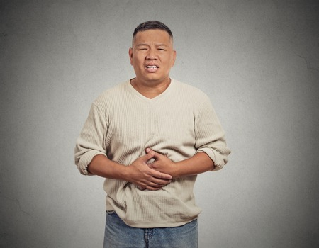 food poisoning: Closeup portrait miserable upset man, person doubling over in acute body stomach pain, looking very sick isolated grey wall background. Negative facial expression emotion feeling health issues concept