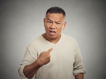 Closeup portrait, angry, unhappy, annoyed young man, getting mad, asking question you talking to, mean me? Isolated grey wall background. Negative human emotion, facial expressions, feelings, reaction