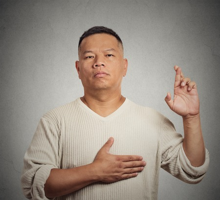 crossing fingers: Closeup portrait serious man, employee middle aged guy, crossing fingers, swearing, giving promise isolated gray wall background. Human emotion, facial expression, body language. Liar concept