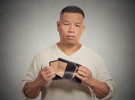 bad economy: Closeup portrait stressed, upset, sad, unhappy middle aged  man standing with, holding empty wallet isolated grey wall background. Financial difficulties, bad economy concept. Negative emotion Stock Photo