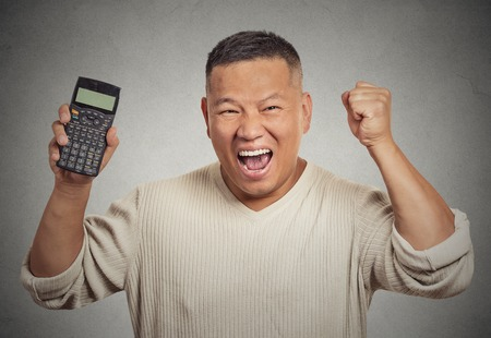 Excited happy business man person showing calculator with million number sign on screen isolated on grey wall office background. Human face expression emotion feeling. Economy financial wealth concept photo