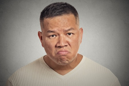 grumpy man isolated on grey wall background Stock Photo