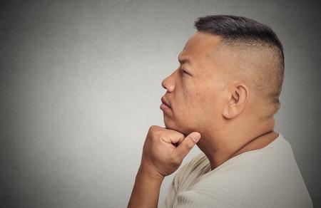 indecision: Side profile headshot portrait thoughtful middle aged man isolated on grey wall background. Human face expression emotion feeling perception Stock Photo