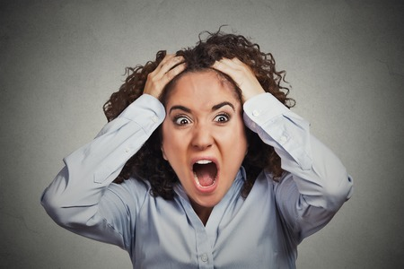 demanding: Closeup portrait stressed, frustrated shocked business woman pulling hair out yelling screaming temper tantrum isolated grey wall background. Negative human emotion facial expression reaction attitude