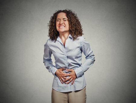 Portrait junge Frau mit den Händen auf Magen schlecht Schmerzen Schmerzen isoliert grauen Wand Hintergrund. Lebensmittelvergiftung, Grippe, Krämpfe. Negative Emotionen Gesichtsausdruck Reaktionsgesundheitsfragen Probleme Standard-Bild