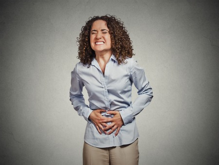 Portrait young woman hands on stomach having bad aches pain isolated grey wall background. Food poisoning, influenza, cramps. Negative emotion facial expression reaction health issues problems photo