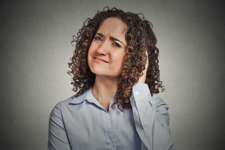 desconfianza: Escéptico. Mujer dudoso que le mira la cámara aislada fondo de la pared gris. Expresión facial emoción humana Negativo sensación corporal actitud idioma