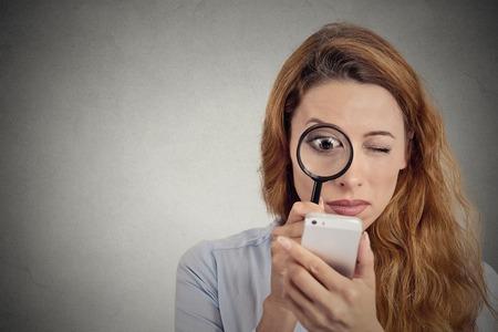 Nieuwsgierig. Zakenvrouw zoekt via vergrootglas op smart phone scherm geïsoleerd grijze achtergrond. Human gezichtsuitdrukking. Investigator zoeken. Veiligheid concept. ingewikkelde technologie Stockfoto