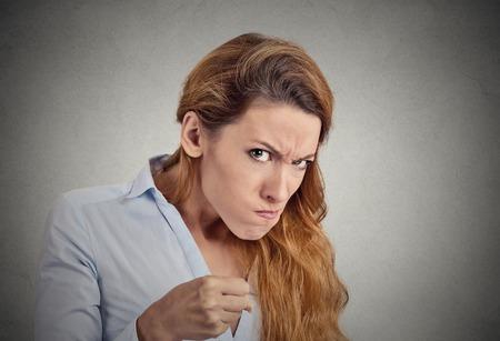 Retrato de mujer enojada en el fondo gris. La emoción negativa