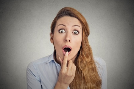 ugly woman: Surprise astonished woman. Closeup portrait woman looking surprised in full disbelief wide open mouth isolated on grey background. Positive human emotion facial expression body language. Funny girl Stock Photo