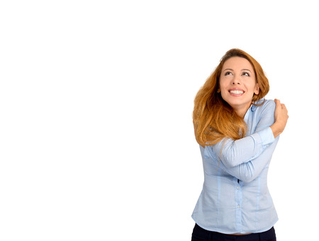 ragazza innamorata: Ritratto del primo piano della donna fiducioso detiene che si abbraccia guardando copia spazio isolato su sfondo bianco. Emozione positiva espressione del viso reazione sentimento. Amare se stessi concept