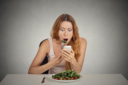 social emotional: portrait young girl eating green salad looking at phone seeing bad breaking news or photos shocked confused face expression isolated on grey wall background Stock Photo