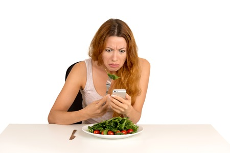 disgusting: portrait young girl eating green salad looking at phone seeing bad news or photos annoyed  confused disappointed face expression isolated on white background