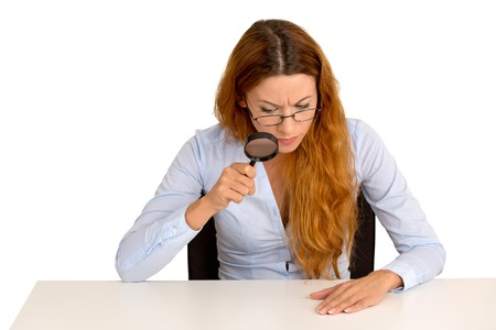 bureaucrat: Portrait serious business woman with glasses skeptically looking through magnifying glass at table sitting at desk isolated white  background. Human face expression, body language, attitude perception Stock Photo
