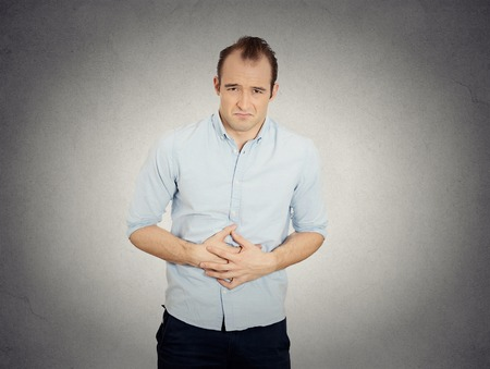 bowel: Closeup portrait miserable upset young man, doubling over in acute body stomach pain, looking very sick isolated grey wall background. Negative facial expression emotion feeling health issues concept Stock Photo