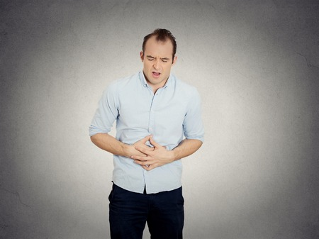 irritable bowel syndrome: Closeup portrait miserable upset young man, doubling over in acute body stomach pain, looking very sick isolated grey wall background. Negative facial expression emotion feeling health issues concept Stock Photo