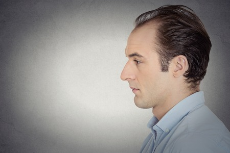 Closeup side view profile head shot portrait sad bothered stressed serious young man depressed about something someone isolated grey background copy space. Negative emotion facial expression feeling