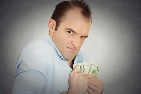 possessive: Closeup portrait greedy banker executive CEO boss, corporate employee funny looking man holding dollar banknotes scared to loose money, suspicious isolated grey background. Human face expression Stock Photo