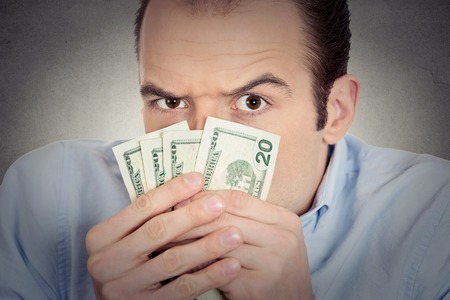 stingy: Closeup portrait greedy banker executive CEO boss, corporate employee funny looking man holding dollar banknotes scared to loose money, suspicious isolated grey background. Human face expression Stock Photo