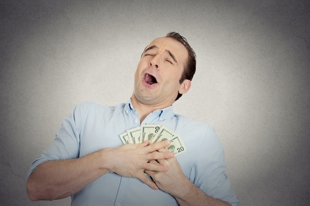 cash money: Primer retrato feliz hombre de negocios exitoso emocionado en el amor con el dinero, chico buscando divertido sosteniendo billetes de d�lar en la mano aisladas fondo de la pared gris. Las emociones humanas, las expresiones faciales, el sentimiento