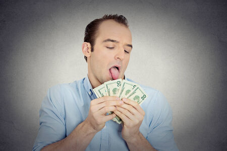 cupidity: Closeup portrait greedy banker, CEO boss, corporate employee, crazy guy, funny looking man obsessed, licking cash, money, dollars with tongue, isolated grey wall background. Face expression emotion Stock Photo