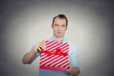 Closeup portrait grumpy unhappy upset man holding red gift box very displeased with what he received, disgust on face isolated grey background. Negative emotion facial expression feeling attitude