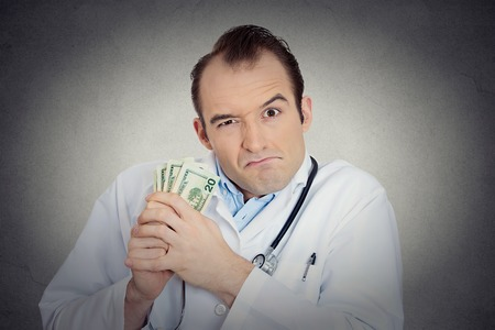 humbug: Closeup portrait grumpy greedy miserly health care professional, male doctor holding, protecting his money dollars in hand isolated grey wall background. Negative human emotions, facial expressions