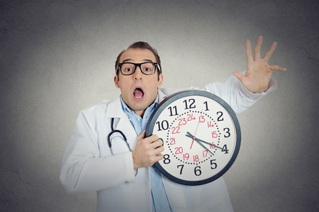 night shift: Closeup portrait overwhelmed, busy, unhappy male health care professional, funny looking doctor guy holding wall clock running out of time exhausted isolated grey wall background. Healthcare reform