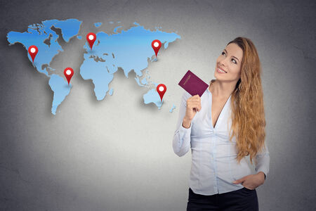 foreign country: Portrait happy tourist young woman holding passport standing looking at world map planning isolated grey wall background. Positive human emotion face expression. Travel vacation getaway trip concept Stock Photo