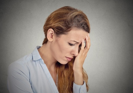maltreatment: portrait of sad young woman isolated on grey wall background