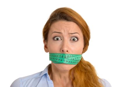 boca cerrada: Retrato infeliz joven con medición verde en la boca cubierta de cinta aisladas sobre fondo blanco. Nutrición Hacer dieta estilo de vida la pérdida de peso concepto Foto de archivo