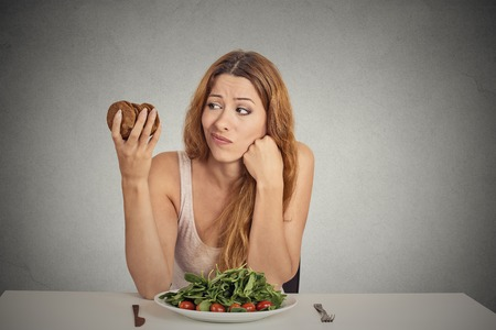 mujer triste: Mujer joven del retrato de decidir si va a comer alimentos saludables o dulces galletas que ella est� anhelando sentado en mesa aislado fondo de la pared gris. Reacci�n cara expresi�n emoci�n humana nutrici�n concepto de dieta