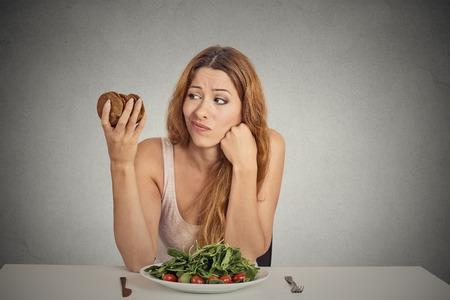 femme triste: Portrait jeune femme de d�cider de manger des aliments sains ou des biscuits sucr�s, elle a soif assis � table isol�e gris mur arri�re-plan. R�action face � l'expression de l'�motion humaine concept de la nutrition Di�te