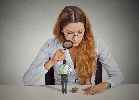 detective: Curious corporate businesswoman skeptically meeting looking at small employee standing on table through magnifying glass isolated grey office wall background. Human face expression attitude perception