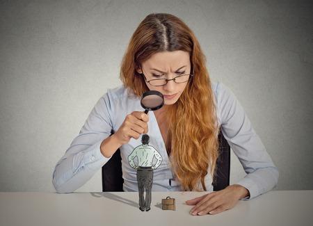 Nieuwsgierig zakelijke zakenvrouw sceptisch ontmoeten op zoek naar kleine werknemer staande op tafel door vergrootglas geïsoleerde grijze kantoor muur achtergrond. Menselijk gezicht meningsuiting houding perceptie