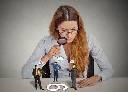 percepción: Empresaria con gafas sentado en el escritorio con escepticismo mirando discutiendo a gente a través de la lupa aislado fondo gris pared de la oficina. Expresión de la cara humana, actitud. A cada uno su propio concepto