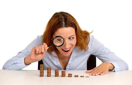 stingy: Closeup portrait excited greedy business woman wall street executive looking at growing stack of coins through magnifying glass isolated white background. Face expression. Economy banking concept