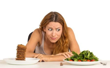 肖像画の若い女性の健康に良い食べ物や甘いクッキーを食べるかどうかを決定する彼女が渇望免震テーブル ホワイト バック グラウンドで座ってい